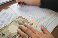 Woman hand hold pen fill in the details on the tax forms paper with yen moneyin business concept. Stock Photo