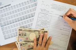 Woman hand hold pen fill in the details on the tax forms paper with yen moneyin business concept. Royalty Free Stock Photography