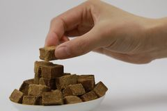 A woman hand hold a piece of brown sugar, cubes rock sugar on a plate, on white background, diabetes stock image
