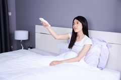 Woman hand hold remote air conditioner on bed in bedroom. Woman hand hold remote air conditioner on bed in the bedroom Stock Photos