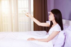 Woman hand hold remote air conditioner on bed in bedroom. Woman hand hold remote air conditioner on bed in the bedroom Royalty Free Stock Photos
