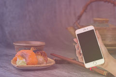 Woman hand hold smart phone on blurred japanese sushi set Stock Photography