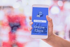Woman hand hold Smart phone e-learning online class on mobile,with bokeh backgrounds, concept online and internet literacy
