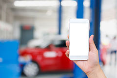 Woman hand hold touch screen mobile smart phone with car garage Royalty Free Stock Photo