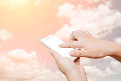 Woman hand hold and touch screen smart phone on cloud background Stock Image