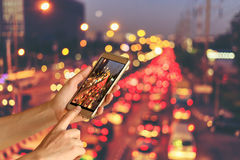 Woman hand hold and touch screen smart phone over blurred photo of car on the road with bokeh background of city street night ligh Royalty Free Stock Images