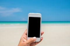 Woman hand hold white mobile phone with sea and blue sky Stock Photos