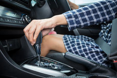 Woman hand holding automatic gear shift in a car. And wearing dress stock photos