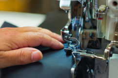 Woman hand holding the black fabric, close up of sewing machine Royalty Free Stock Photo