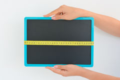 Woman hand holding a blackboard with a measuring tape Royalty Free Stock Images