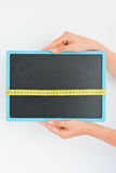 Woman hand holding a blackboard with a measuring tape Stock Photo