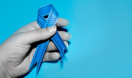 Woman hand holding blue ribbon, blue november prostate cancer awareness month concept. Mens health awareness month stock photography