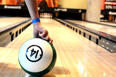 Woman hand holding a bowling ball in hand on bawling alley. Woman holding a bowling ball in hand on bawling alley Royalty Free Stock Image