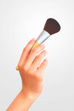 Woman hand holding brush for makeup. Royalty Free Stock Photography