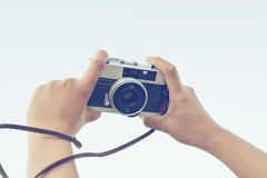 Woman hand holding camera for selfie. Vintage effect Stock Photo