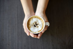 Woman hand holding cappuccino Royalty Free Stock Photo
