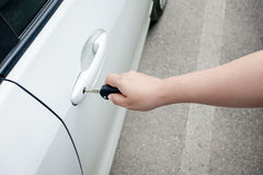 Woman hand holding car keys to unlock or lock. The white car Stock Photos