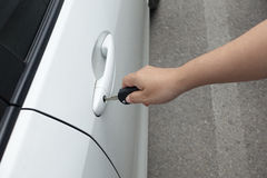 Woman hand holding car keys to unlock or lock. The white car Stock Images
