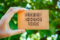 Woman hand holding cardboard card with words Enjoy Every Day aga. Woman hand holding cardboard card with words Enjoy Every Day made by black alphabet stamps Royalty Free Stock Photo