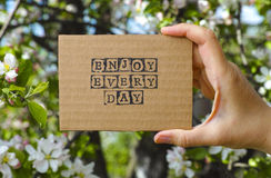 Woman hand holding cardboard card with words Enjoy Every Day Stock Photos