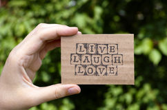 Woman hand holding cardboard card with words Live Laugh Love Stock Photo