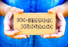 Woman hand holding cardboard card with words Re-Invent Yourself Royalty Free Stock Images