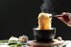 Woman hand holding chopsticks of instant noodles in cup with sm royalty free stock image