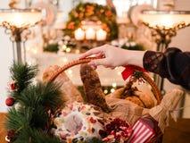 Christmas goods basket holiday food. Woman hand holding Christmas goods in a basket. Festive holiday food gift concept Stock Photos