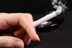 Woman hand holding a cigarette Stock Photos