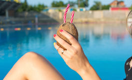 Woman hand holding coconut cocktail by the pool Stock Images