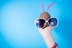 Woman hand holding a coconut and sunglasses Stock Photo