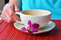 Woman hand holding coffee cup with flower Royalty Free Stock Photo