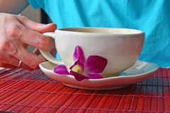 Woman hand holding coffee cup with flower Stock Photo