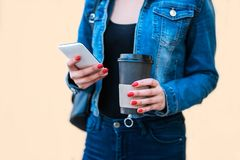 Woman hand holding coffee cup and smartphone. stock image