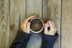Woman hand holding coffee cup on wooden table. royalty free stock photography