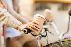 Woman hand holding coffee and riding bicycle Royalty Free Stock Photos