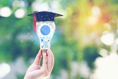 Woman hand holding cog inside in light bulb with graduates hat on natural green background, Education and Creative idea and stock photo