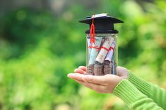 Woman hand holding coins money and banknote in glass bottle with graduates hat on natural green background, Saving money for royalty free stock photos