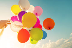Woman hand holding colorful balloons in morning time. Royalty Free Stock Photography
