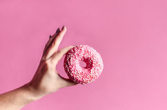 Woman hand holding colorful donut with sprinkles Stock Photos