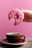 Woman hand holding colorful donut with sprinkles Stock Image