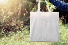 Woman of hand holding cotton Tote Bag on green grass background. Concept eco and recycling stock photos
