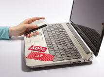 Woman hand holding a credit card and typing. The concept of cheap shopping on the Internet. Royalty Free Stock Image
