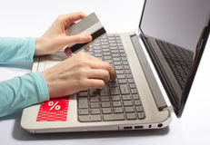 Woman hand holding a credit card and typing. The concept of cheap shopping on the Internet. Royalty Free Stock Photos