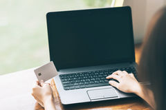 Woman hand holding credit card and using laptop for online business Stock Photography