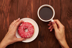 Woman hand holding cup of coffee and pink donut Royalty Free Stock Photo