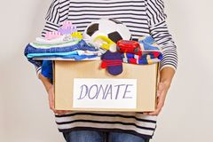 Woman hand holding donation box with clothes, toys and books for charity stock photography