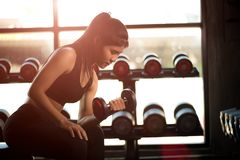 Woman hand holding dumbbell exercise in gym. Fitness muscular body with set of black weights. In the gym background. exercise and healthy lifestyle concept stock photos