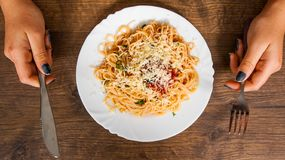 Woman hand holding fork and knife with spaghetti bolognese in white plate on wooden table. top view Stock Image