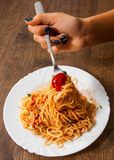 Woman hand holding fork with spaghetti bolognese in white plate on wooden table. Royalty Free Stock Photos